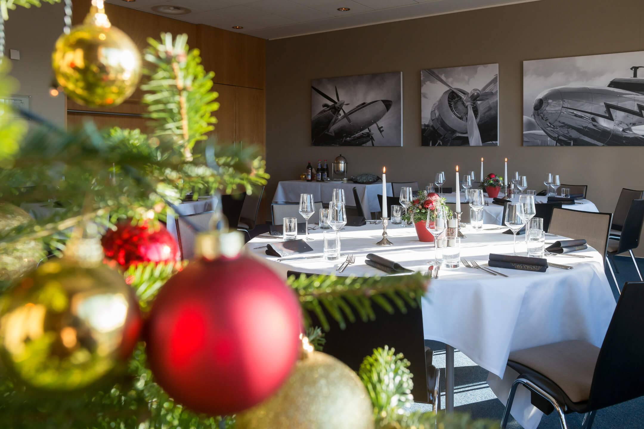 Christmas tree and decorated tables in function room Trans-Atlantik in ATLANTIC Hotel Airport Bremen