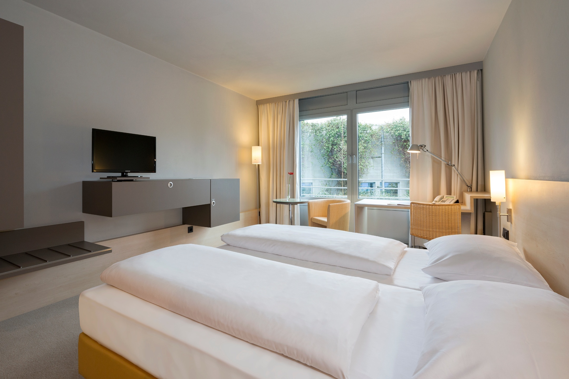 Interior view of a Economy Room with a double bed and cozy furniture in the ATLANTIC Hotel Universum