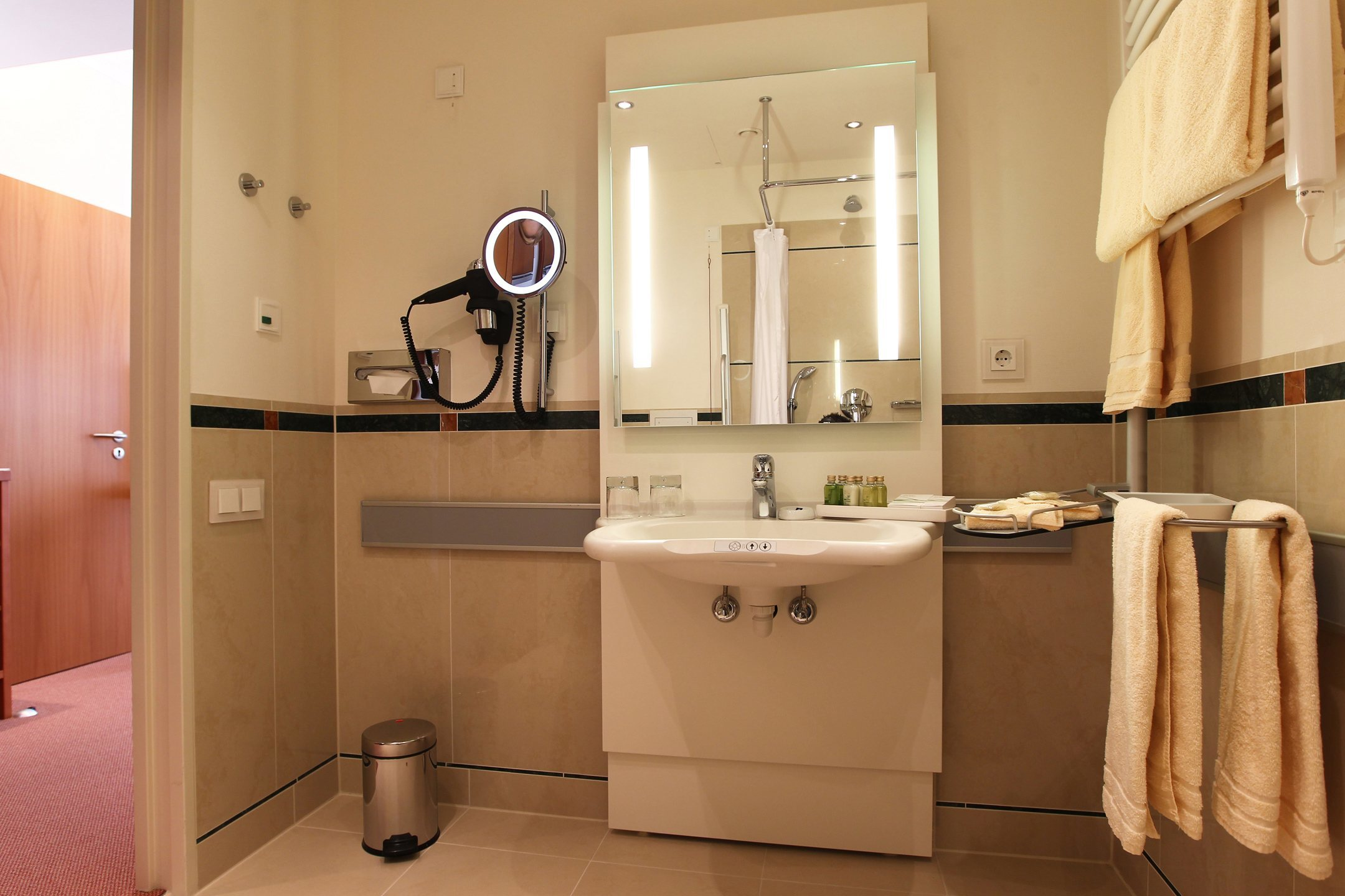 Bathroom of the barrier-free Standard Room with special control elements to ensure a barrier-free access in the ATLANTIC Hotel Wilhelmshaven