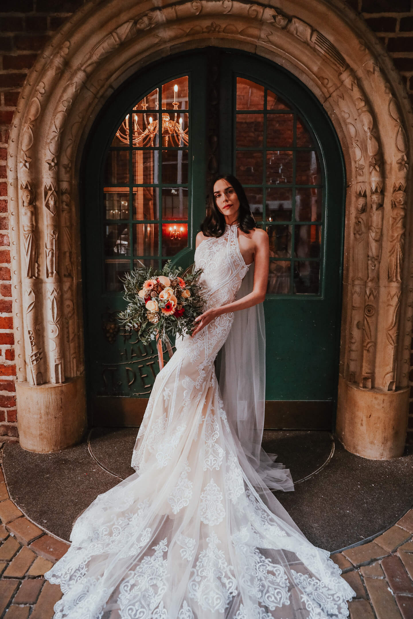 portrait photo of the bride with long white dress and salmon-colored weddingflowers