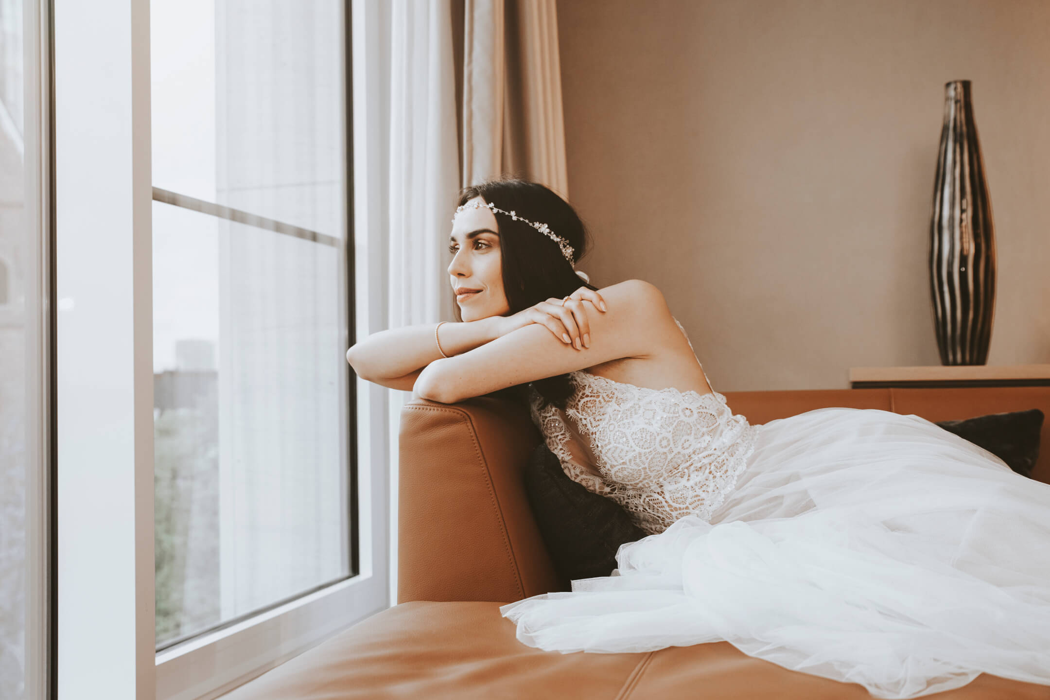 Bride looks dreamy out of the window of the Grand Suite at the ATLANTIC Grand Hotel Bremen