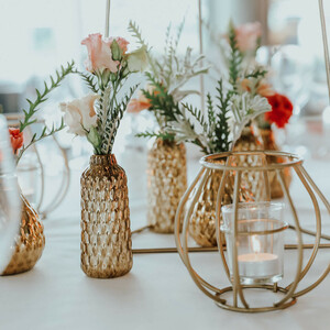 golden vases with summery flowers on laid tables