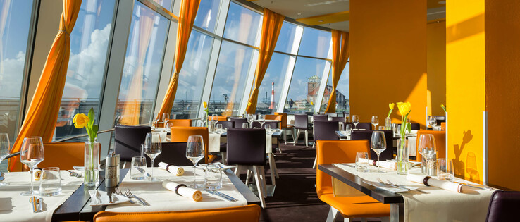 Set tables in the restaurant STROM in the ATLANTIC Hotel Sail City in Bremerhaven